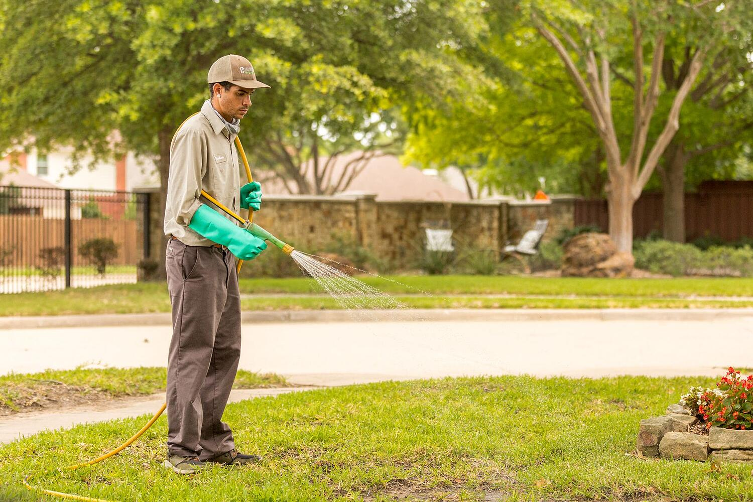 Lawn care company employee treating grass