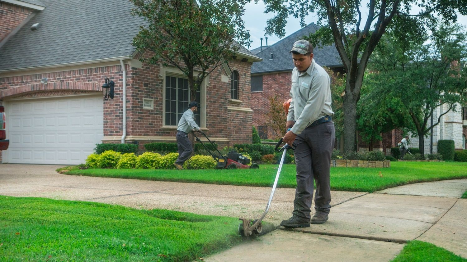 landscaping technicians mowing and trimming lawn