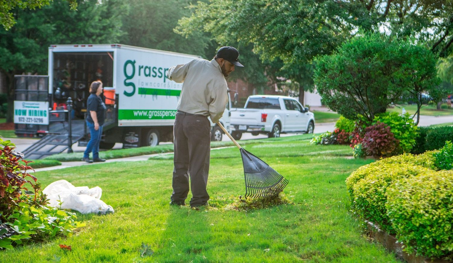 Grassperson lawn care and landscape truck and crew performing landscape maintenance