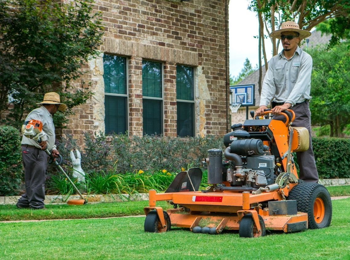 Lawn care technicians mowing and trimming lawn