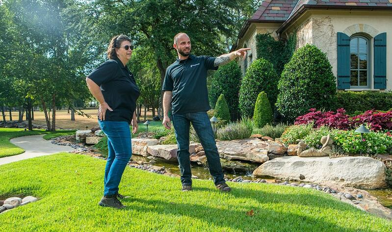 Grassperson lawn care and landscape employees in lawn