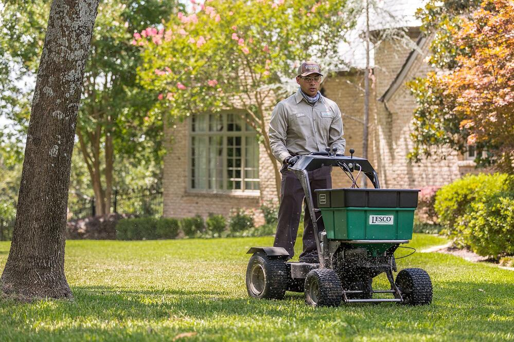 Lawn Care Specialist spreading fertilizer