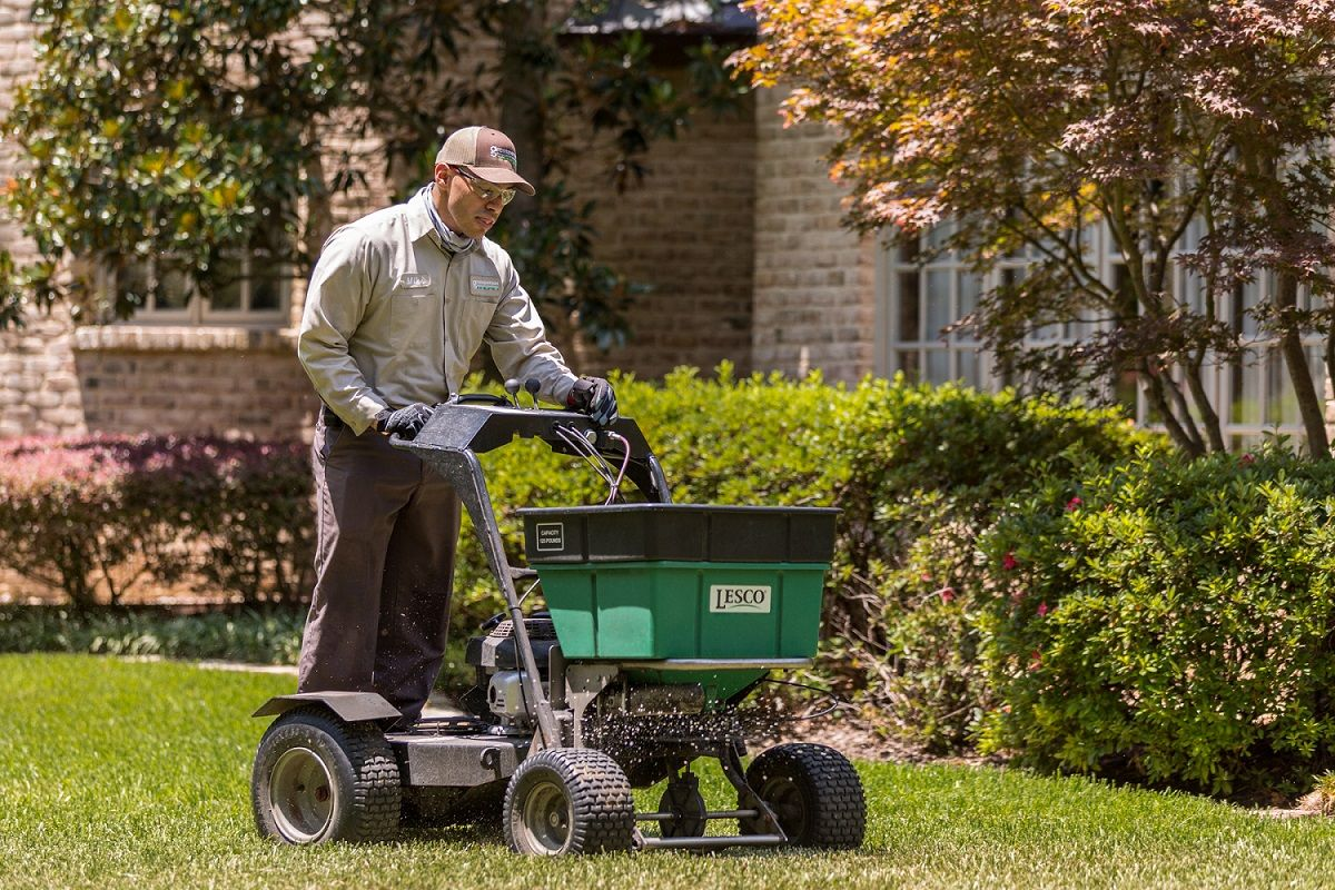 lawn care technician spreading fertilizer for job Texas