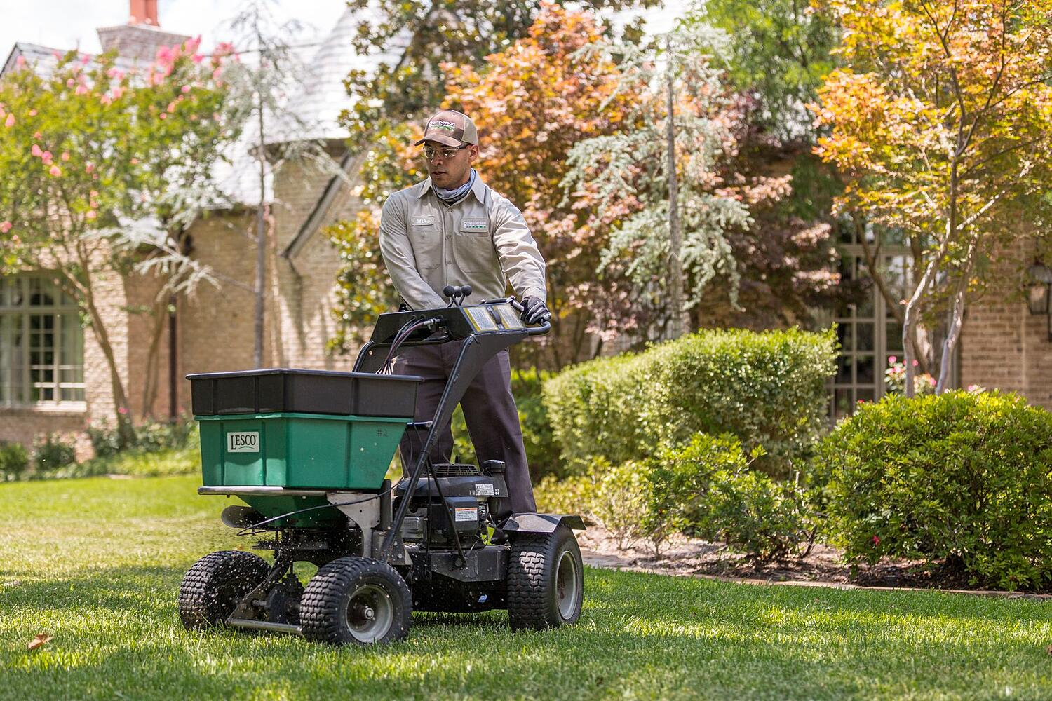 Grassperson lawn care employee treating lawn in Highland Village, TX