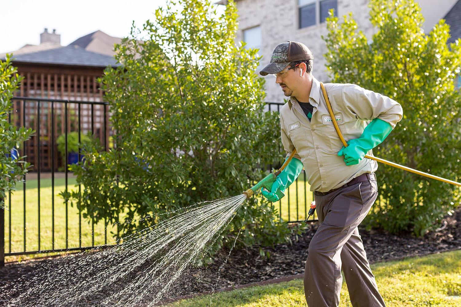 lawn care technician spraying weed control in Texas